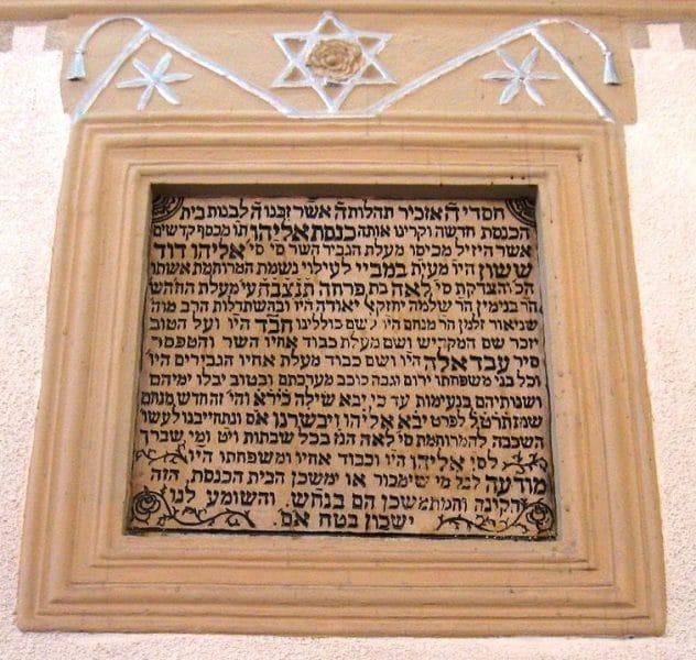 לוח האבן שנקבע בקיר הפנימי של בית הכנסת