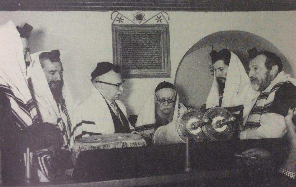 """הנשיא שז""""ר עולה לתורה בבית הכנסת """"צמח-צדק"""" לצידו הרב זוין וברקע לוח האבן לזכרתם של בני משפחת ששון"""