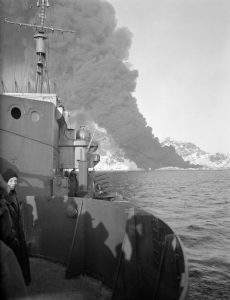 Burning oil tanks as seen from the destroyer HMS Legion, photo by Lt. R.G.G. Coote, Royal Navy official photographer