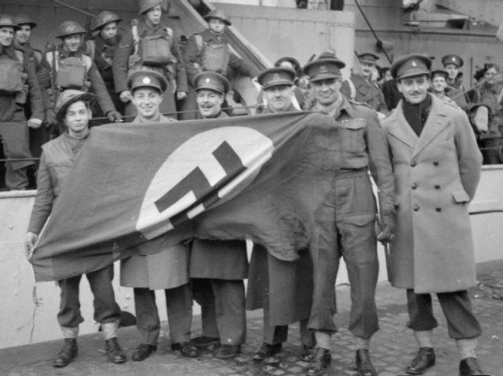 British officers with a captured Nazi flag after the raid on the Lofoten Islands, photo by Capt. Tennyson d'Eyncourt, British War Office official photographer