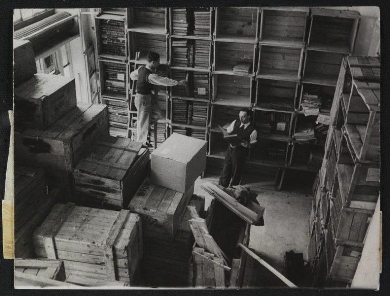 בשל מחסור בעץ, סודרו הספרים על מדפים שהוכנו מן הארגזים עצמם במחסני הספרייה הלאומית הארעיים. צילום: אדגר הירשביין. לחצו להגדלה