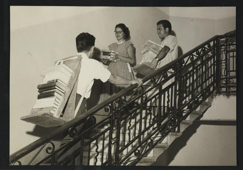 העברת ספרים מן המחסנים לאולמות הקריאה המאולתרים בבניין טרה סנטה, 1960. צילום: דוד חריס. לחצו להגדלה