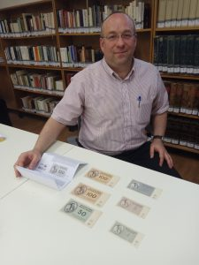 Dr. Yoel Finkelman, curator of the National Library's Judaica Collection, reviews bills from the Theresienstadt Ghetto donated to the Library by Mrs. Ruth Brass in memory of her late father, Lionel Schalit.